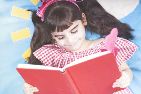 Cute little girl dressed up as a fairy reading a book Stock Photo - 112521855