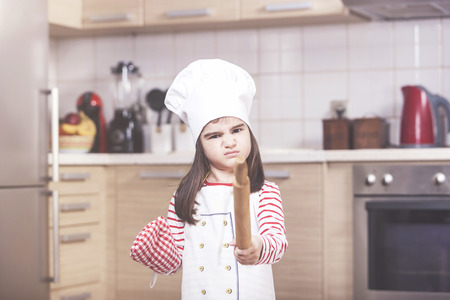 Angry little girl chef in the kitchen