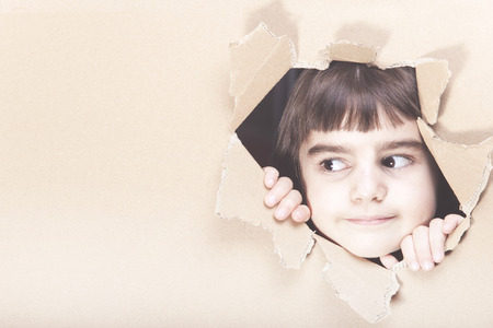 Cute little girl looking through a paper hole with copy space Stock Photo - 112521863