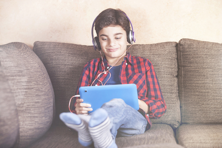 Trendy young boy listening to his favorite music at home using his tablet Stock Photo