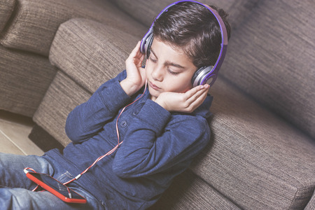 Boy relaxing at home listening to his favorite music using his smartphone and a set of headphones Stock Photo - 112521867