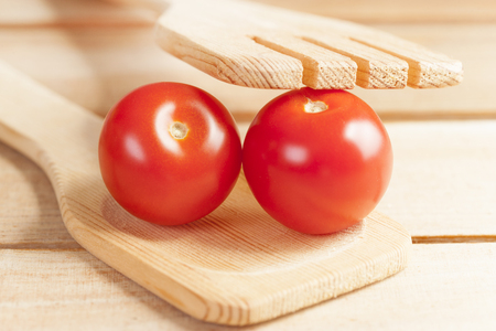 Fresh tomatoes with wooden spoon and fork Stock Photo - 112521868