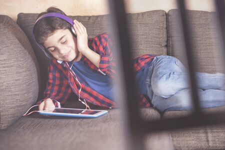 Young boy listening to his favorite music using his tablet. Kids and technology concept Archivio Fotografico