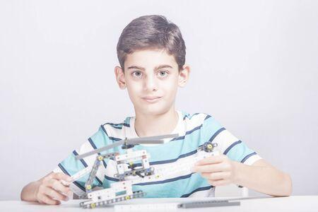 Boy creates a diy mechanical helicopter model. STEM education concept Archivio Fotografico