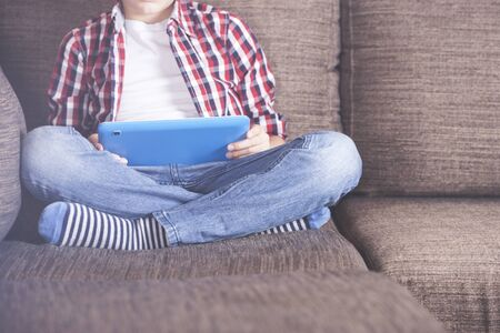 Young boy using his tablet at home
