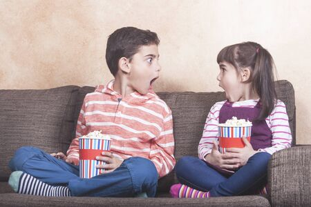 Shocked kids react while watching inappropriate content on television