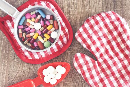 Medicine capsules and pills served on a wooden table
