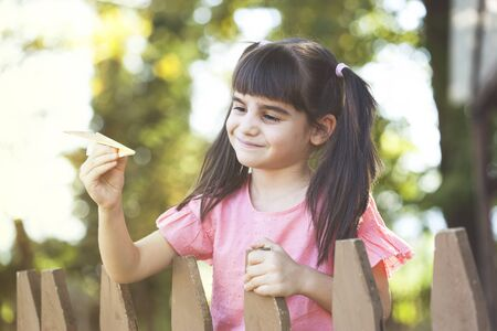 Happy little girl playing with a paper airplane at the park