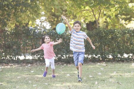 Kids playing with a balloon in the park. Children having fun outdoors concept