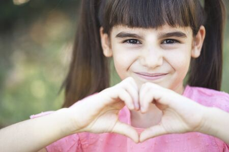 Childhood concept. Cute little girl making a heart shape with her hands