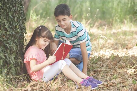 Kids reading together at the park