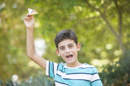Cheerful little boy playing with a paper airplane at the park
