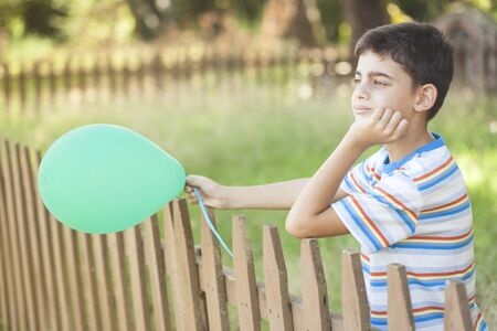 Young boy with ballοon outdoors. Childhood concept
