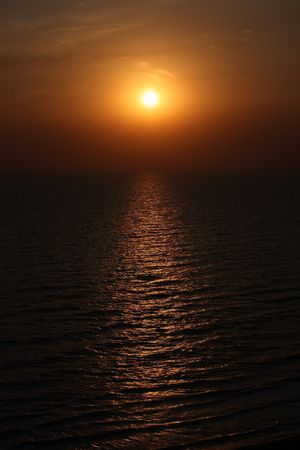 Yellow sun rising over the ocean rippling waves Stock Photo - 7565964