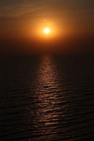 setting sun: Yellow sun rising over the ocean rippling waves Stock Photo