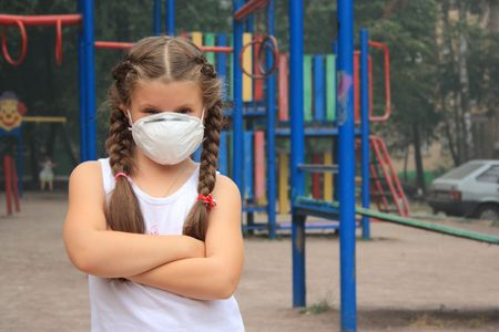 smog: The girl in a breathing mask on a childrens playground Stock Photo