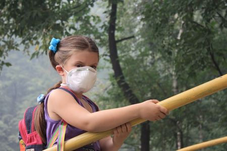 air filter: girl in a breathing mask in a smoke-filled backyard Stock Photo
