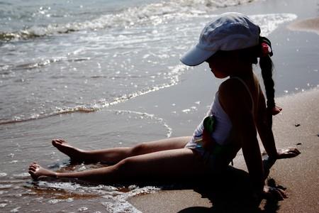 Little preschool girl sitting on the wet sand Stock Photo - 7669056
