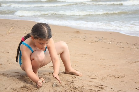 bikini construction:  Little girl on the beach building sand castle Stock Photo