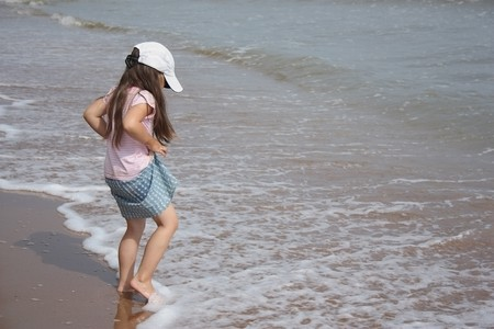 Preschool girl on the beach soaks his feet photo