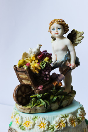 Cupid Hold Wheelbarrow Which Contain Fruit