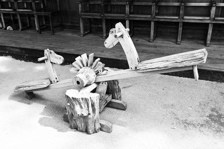 The wooden seesaw board with the wooden chair in the background, black and white mode