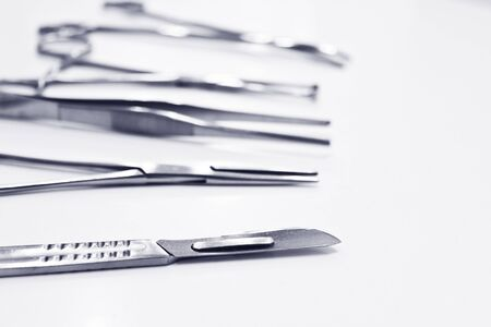 Surgical instruments isolated on the white background, focus on the scalpel blade