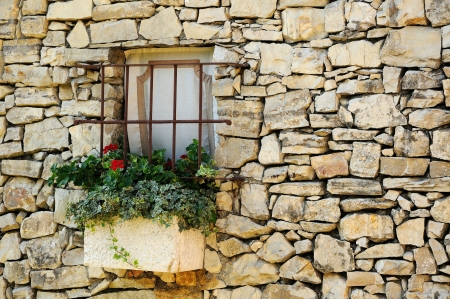 Muro di pietra d'epoca con piccola finestra e fiori
