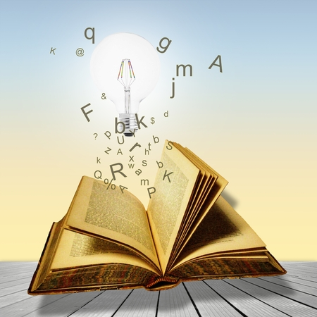 Open book with lightbulb and letters. Concept of the importance of reading. Stockfoto