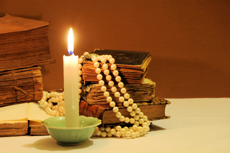 string of pearls: Old books, candle and string of pearls. Focus on candle Stock Photo