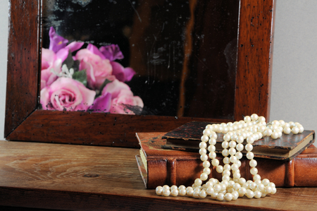 string of pearls: String of pearls, books and antique mirror.  Focus on pearls.