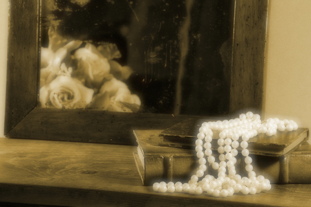 antique mirror: String of pearls, books and antique mirror.  Focus on pearls. Vintage effect. Stock Photo