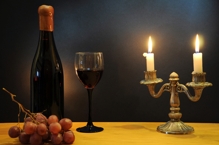 Old bottle of esteemed italian wine with glass, candlestick and grapes