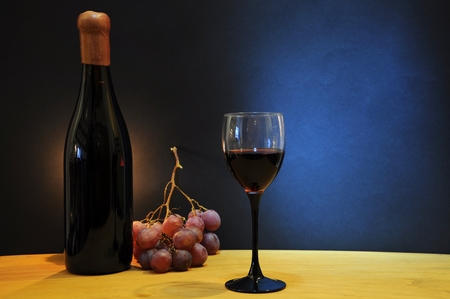 esteemed: Old bottle of esteemed italian wine with glass and grapes on wooden table