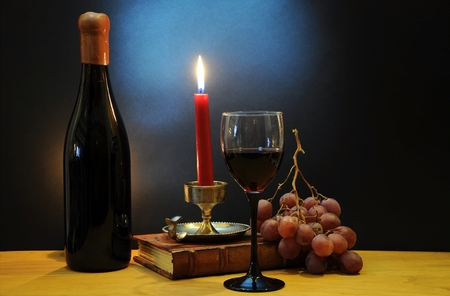 esteemed: Old bottle of esteemed italian wine with glass, candle and grapes