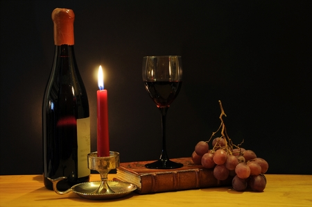 Old bottle of esteemed italian wine with glass, candle and grapes