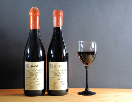 Brescia, Italy - January 17, 2016: old bottles of fine red wine Recioto della Valpolicella Amarone produced exclusively in the Valpolicella in the province of Verona, Italy. Limited production of 1976 with numbered  handwritten labels.