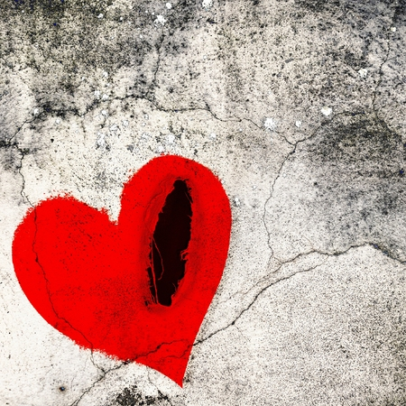 Frayed red heart on cracked wall