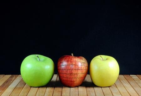 Tre mele con la mela nella struttura del muro di mattoni. Su stuoie in teak e sfondo nero. Copia spazio Archivio Fotografico