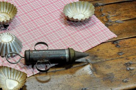 Strumenti pasticceria molto vecchi: siringhe da torta e tagliere di biscotti. Sfondo di legno usurato. Archivio Fotografico