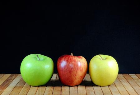 Three apples on teakwood shelf and black background. Stock Photo