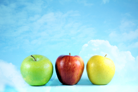 Three apples on bright sky and clouds. Archivio Fotografico