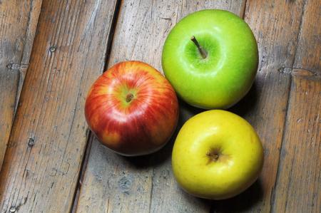 Tre mele su fondo in legno Archivio Fotografico