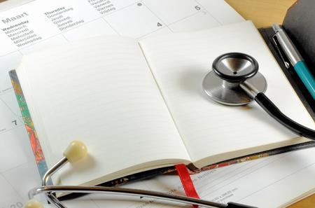 Una scrivania con stetoscopio, quaderno, penna e calendario