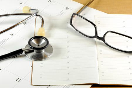 A desk top with stethoscope, address book, glasses and calendar Archivio Fotografico