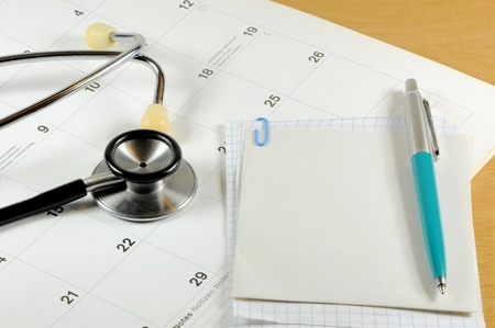 A desk top with stethoscope, notebook, pen and calendar Archivio Fotografico