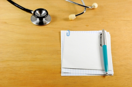 A desk top with stethoscope, notebook and pen Archivio Fotografico