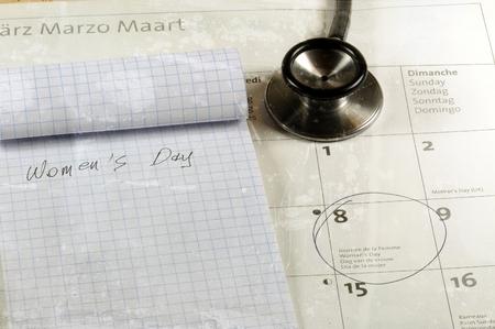 Scrivania con stetoscopio, calendario e quaderno. Concetto di giorno delle donne.