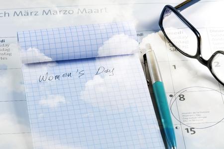 Desktop with calendar, notebook, pen and glasses. Blue cloudy sky textured. Archivio Fotografico