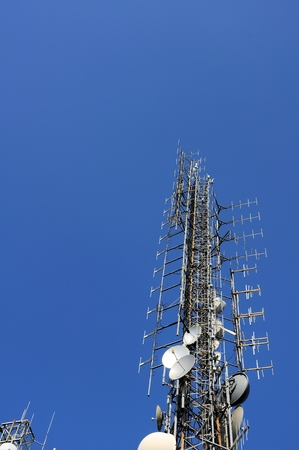 Telecommunication tower Antenna on blue sky. Technology background.